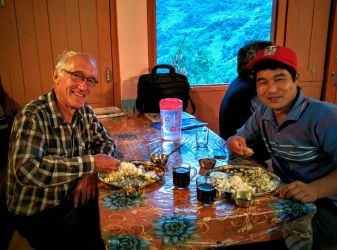 HELP volunteer Jim Dix (left) and fellow teacher Nirmal share the essential Nepali dinner, dal bhatt, eaten the traditional way, with the fingers of your right hand. The dark liquid in the cups is Coca-Cola.