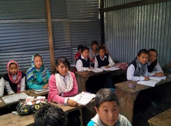 Students in grade 7, eagerly anticipating the next English lesson. The room is a temporary makeshift room made with corrugated sheet metal, to be used while the new school building is built.